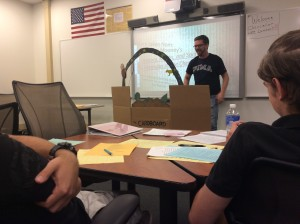 "Mitch Taylor educates fellow students with a presentation, ""A Cardboard Retelling of the Cherokee Myth of Creation."""